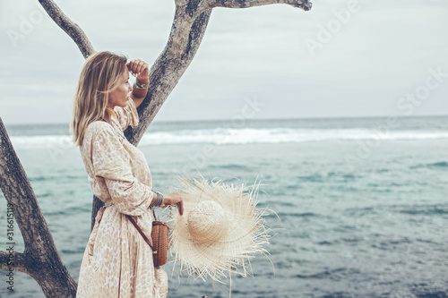 Cuadros en Lienzo Boho model wearing dress and straw hat on the beach