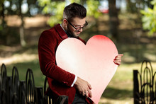 Businessman Holding And Looking At A Big Heart With Love