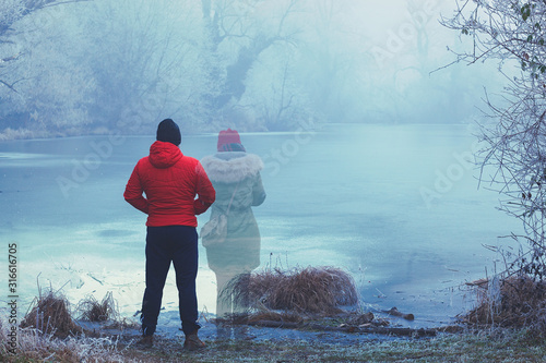 Foto Lonely man in red jacket standing by the lake in winter, with transparent woman