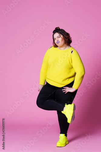 Wesoły plus rozmiar modelu w ubranie, gruba kobieta w czarnych dżinsach i żółty sweter na różowym tle