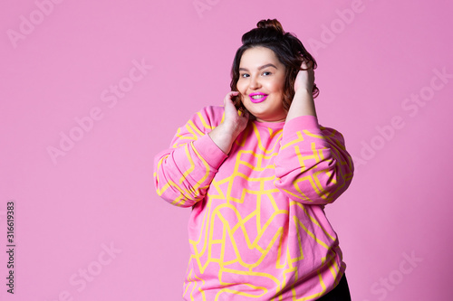 Photo Happy plus size model in casual clothes, fat woman on pink background