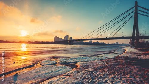Fototapeta Pivnichnyi Bridge silhouette over half frozen Dnipro river against city at bright setting sun light. Concept river landscape, urban bridge structure, transport, environment. obraz