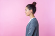Side view of cheerful brunette teenage girl with bun hairstyle in casual pullover smiling, looking kind and positive, empty copy space for advertisement. indoor studio shot isolated on pink background