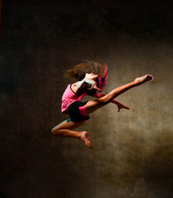Street Dance Girl Dancer Jumping Up Dancing In Neon Light Doing Gymnastic Exercises Jump In Studio On Dark Wall