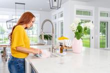 A Woman Washing Dishes In A Modern Farmhouse Kitchen.