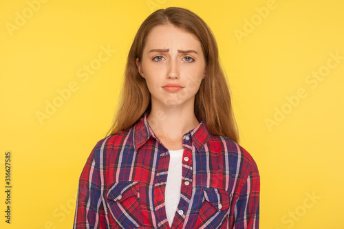 Fotografía Portrait of unhappy ginger girl in checkered shirt frowning and looking at camera with upset dismal expression, feeling insulted, resentful facial emotion