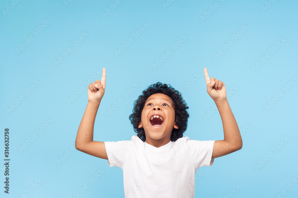 Fototapeta Wow, look up! Portrait of amazed little boy pointing up to empty place on blue background, expressing shock surprise with wide open mouth and showing copy space for advertisement. indoor studio shot