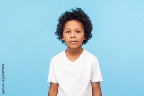Fotografering Portrait of cute little boy with stylish curly hairdo in white T-shirt standing, looking at camera with serious attentive face, calm pensive expression