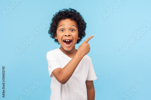Vászonkép Wow look, advertise here! Portrait of amazed cute little boy with curly hair pointing to empty place on background, surprised preschooler showing copy space for promotional ad