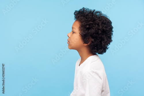 Profile of pretty nice little boy with stylish curly hair in T-shirt looking to side with serious attentive face, calm pensive expression Fototapet