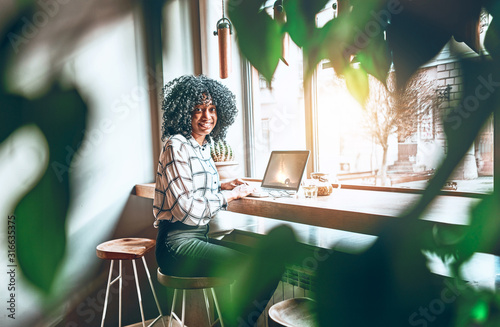 It is wonderful when the work is fun. A young african american is working or studying in a beautiful workplace in a cafe. Blurred greens on the sides.