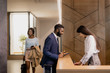 Young African businessman in formalwear bending over reception counter