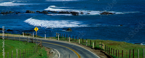 Obraz This is Route 1, also known as the Pacific Coast Highway. The ocean is to the right of the road which curves around a bend. - fototapety do salonu
