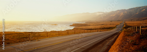 Fototapeta This is Route 1also known as the Pacific Coast Highway. The road is situated next to the ocean with the mountains in the distance. The road goes off into infinity into the sunset. obraz
