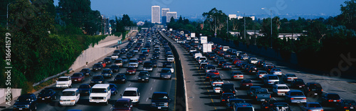 This is rush hour traffic on the 405 Freeway at sunset. There are 10 lanes of traffic total showing both sides of the freeway. There are cars stopped in every lane.