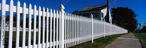 Fotografía This is a close up of a white picket fence and a typical looking suburban house