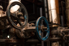 Two Old Rusty Valves In A Dark Factory Room Are Braided With Cobwebs