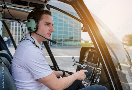 Obraz na plátně A Airline pilot wearing uniform sitting inside with epaulettes and headset to connect with another pilot on board passenger