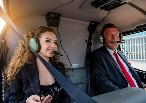 Obraz na plátně A  businesswoman and businessman passenger sitting inside plane with headset to connect with another person in airplane