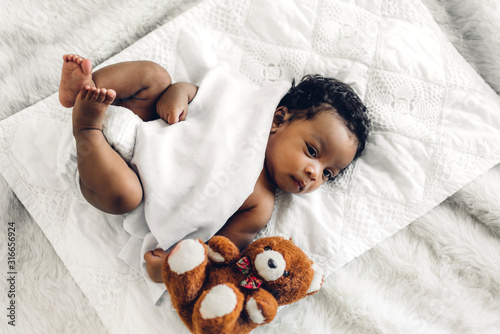 Fotografiet Portrait of cute adorable little african american baby sleep in a white bedroom