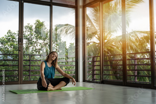 Obraz An attractive 40-year-old middle-aged woman practices yoga in a panoramic window room overlooking the garden at dawn in the sunshine. Meditation mindfulness healthy lifestyle concept - fototapety do salonu