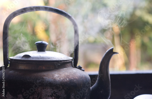 Hot water with smoke from kettle. Fototapeta