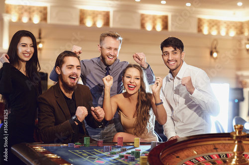 Valokuvatapetti Cheerful group of friends enjoys winning poker roulette in a casino