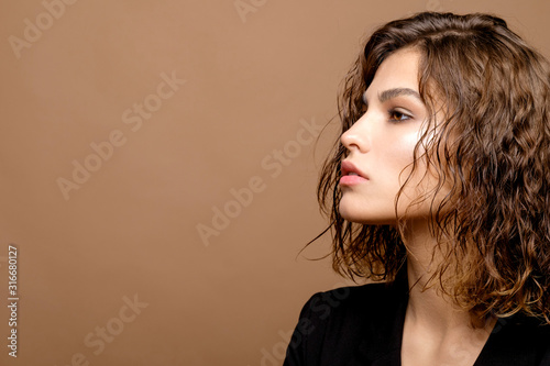 beauty fashion model with clean skin and curly hair in black jacket on biege bac Fototapete