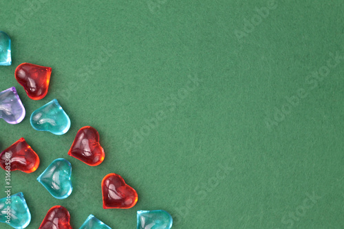 Fototapety, obrazy: A scattering of glass hearts of blue, red, lilac and white on a green felt background. Stock photo for Saint Valentine's Day with empty place for text. For web, print, cards, invitations, wallpaper.