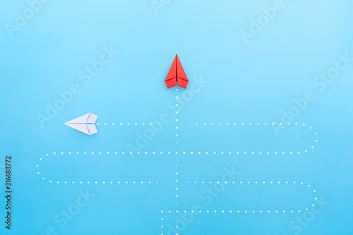 Obraz Business concept for new ideas creativity and innovative solution, Red paper plane in one individual pointing in the different way - fototapety do salonu