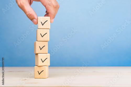 Obraz na plátně Checklist concept, Check mark on wooden blocks, blue background with copy space