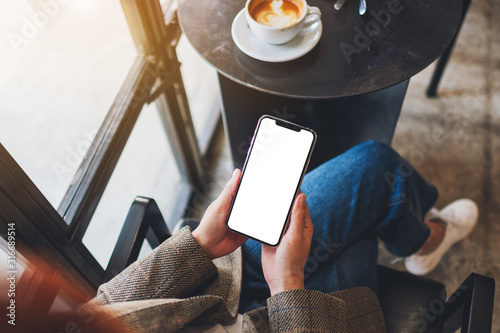 Fotografía Top view mockup image of a woman holding black mobile phone with blank desktop s