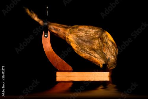 Fotomural Whole Iberian ham leg in a ham holder reflected on black