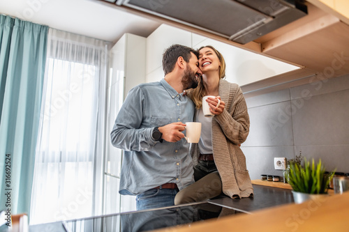 Fototapety, obrazy: Cute young couple drinking coffee in kitchen