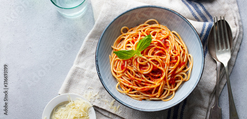 Foto Pasta, spaghetti with tomato sauce and fresh basil in a bowl