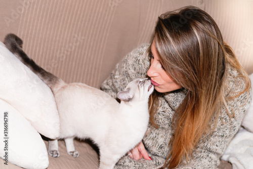 Fotomural Woman at home kissing her lovely fluffy siamese cat