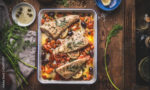 Tasty Bass fish fillets in Mediterranean sauce with tomatoes, olives and capers in baking pan on rustic wooden background with ingredients. Top view