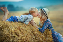 Mom And Son Close Up In A Field With Mowed Wheat.