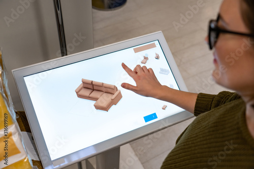 Fototapeta Woman configuring furniture at the self-service desk in the store