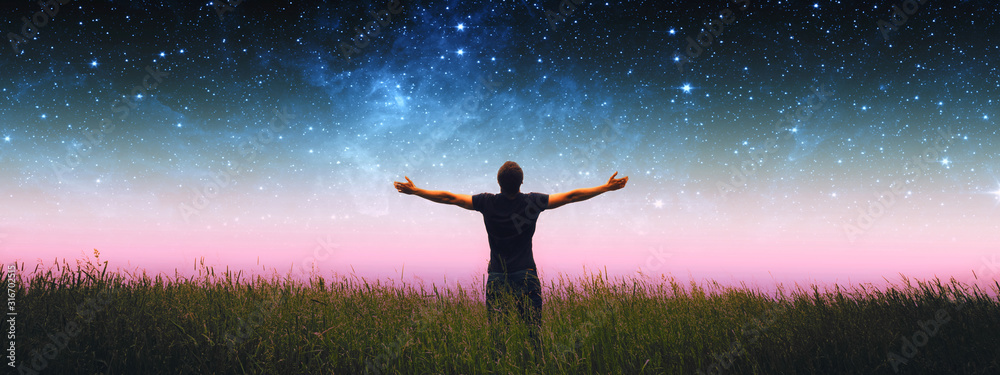Fototapeta Man with arms wide open standing on the grass field against the night starry sky. Elements of this image furnished by NASA.