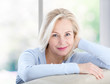 canvas print picture - Active beautiful middle-aged woman smiling friendly and looking in camera near window at home. Woman's face closeup. Selective focus.