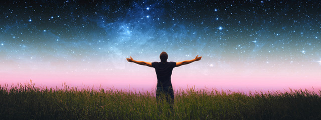 Man with arms wide open standing on the grass field against the night starry ...
