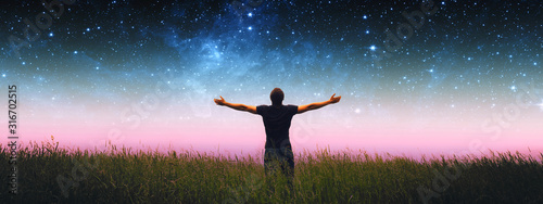 Fototapeta Man with arms wide open standing on the grass field against the night starry sky. Elements of this image furnished by NASA. obraz