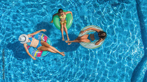 Family in swimming pool aerial drone view from above, happy mother and kids swim Wallpaper Mural