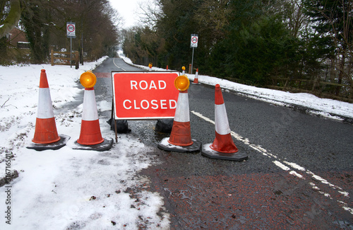 A red Road Ahead Closed sign due to adverse road conditions in winter, England, UK Wallpaper Mural