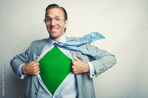 Smiling businessman pulling open his suit to reveal an inner green superhero identity in the office