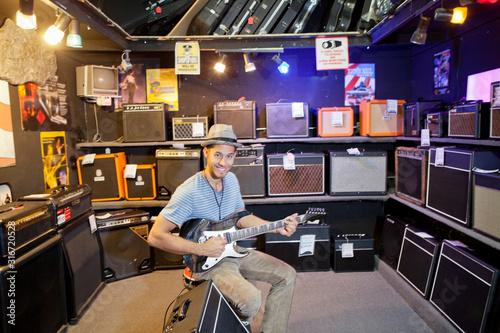 Fotografija Portrait of happy young male customer strumming the guitar in music store