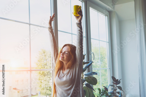 Fototapeta happy smiling young woman waking up, stretching, drinking coffee obraz