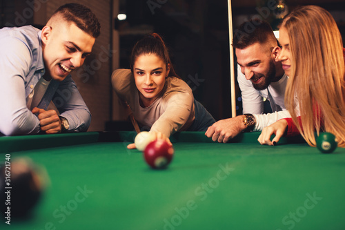 Fotografie, Obraz Group of friends play billiards at night out