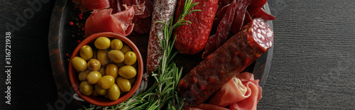 Fototapeta top view of delicious meat platter served with olives and herbs on wooden black table, panoramic shot obraz